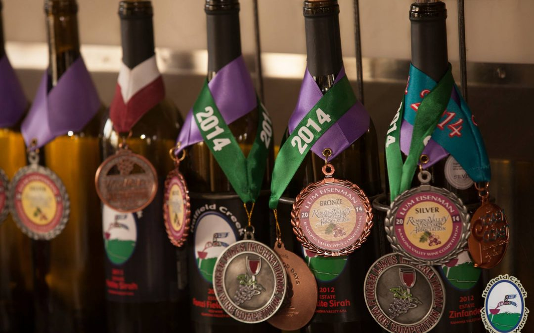wine bottles with award medals around them